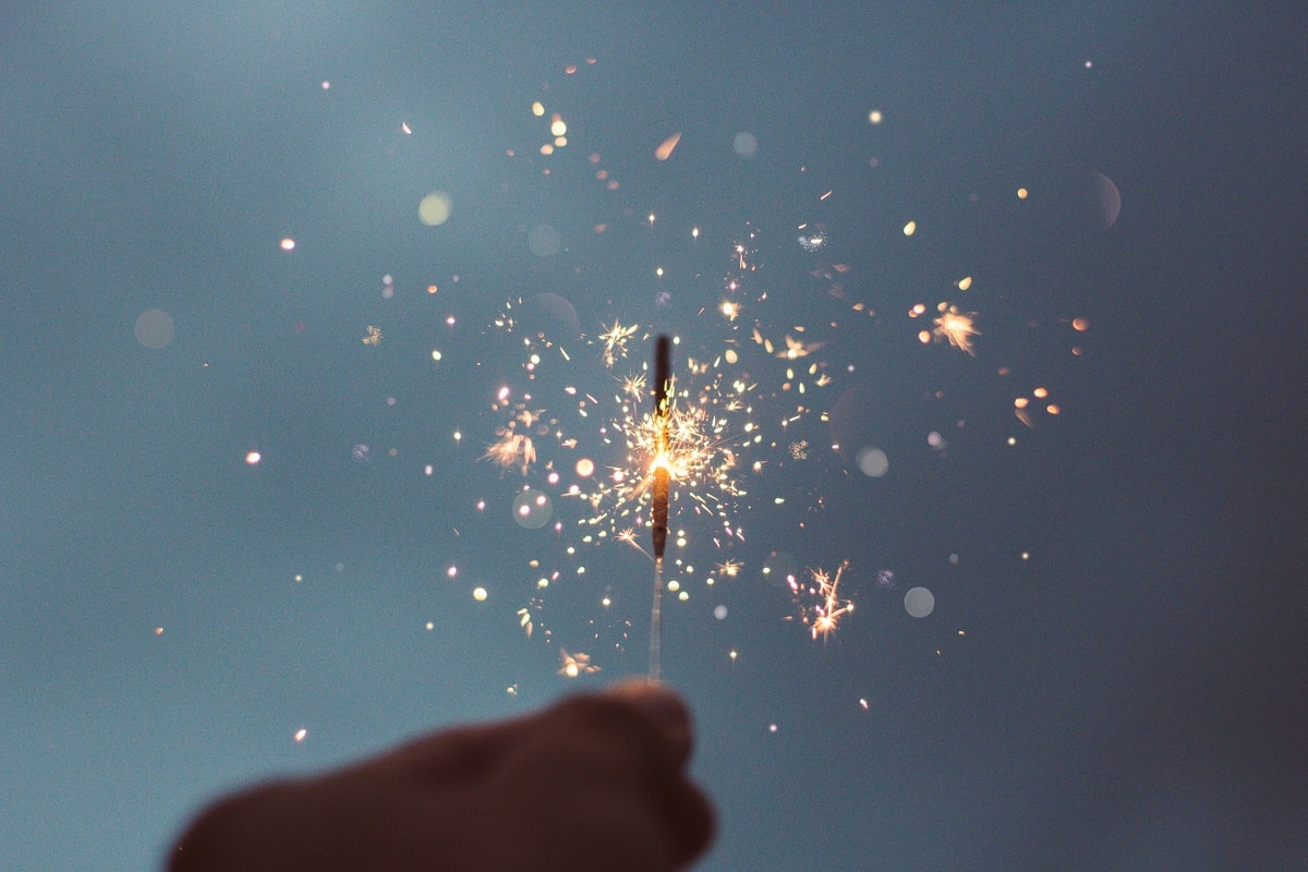 Hand holding a lit sparkler on New Years