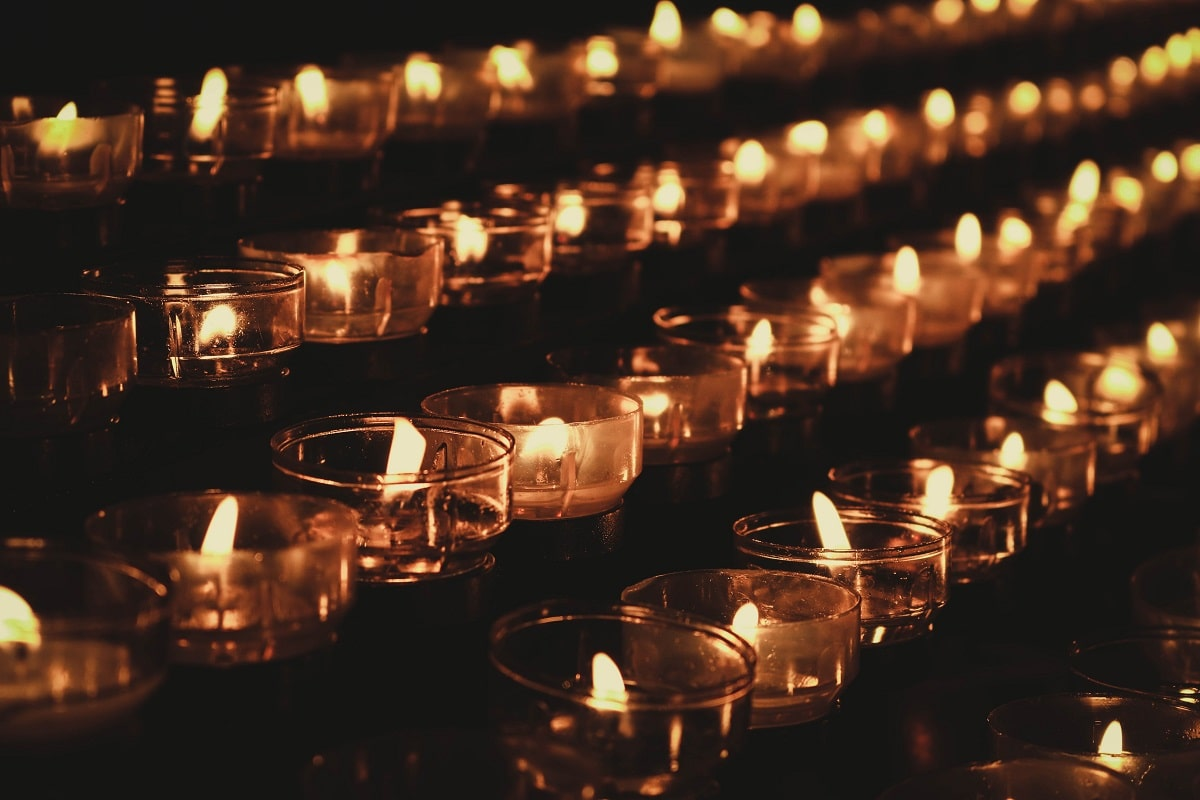Many small lit candles in glass cups on top of a table
