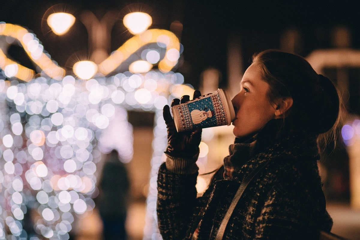 A woman drinking coffee outside during the holidays
